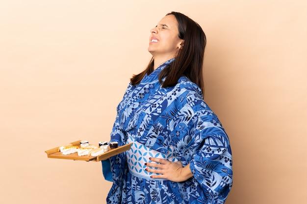 Kobieta ubrana w kimono i trzymająca sushi nad ścianą cierpiąca na ból pleców za to, że podjęła wysiłek