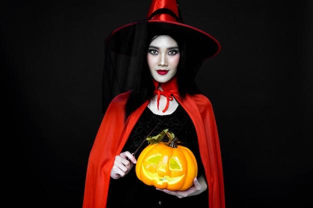 Kobieta ubrana w kostium na halloween i trzymająca różdżkę i dynię