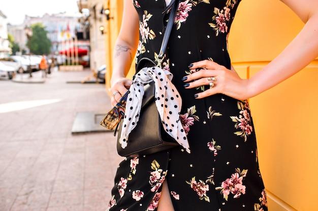 Kobieta ubrana w kwiecistą sukienkę, pozowanie w pobliżu żółtej ściany