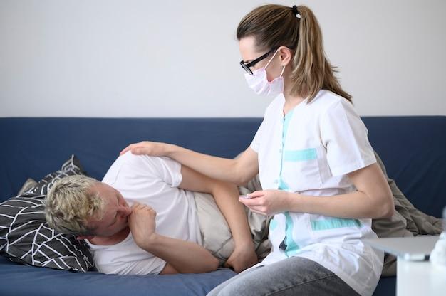 Kobieta ubrana w maskę dbanie o jej pacjenta