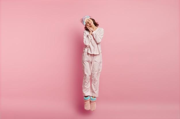 Kobieta ubrana w maskę do spania i piżamę