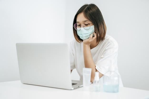 Kobieta ubrana w maskę, grająca na laptopie i mająca butelkę żelu do mycia rąk.