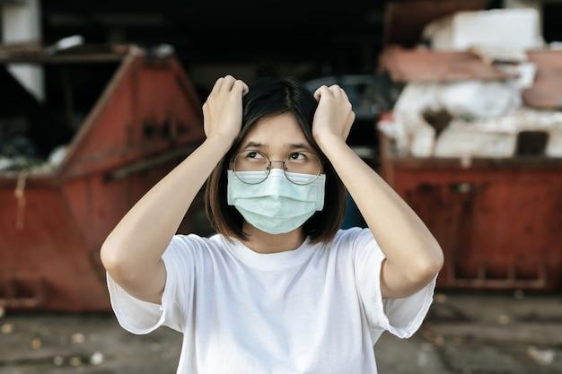 Kobieta ubrana w maskę i dwie ręce, trzymając głowę.