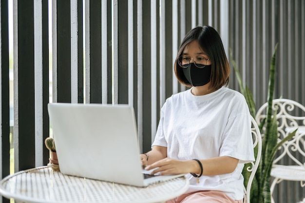 Kobieta ubrana w maskę i grająca na laptopie.