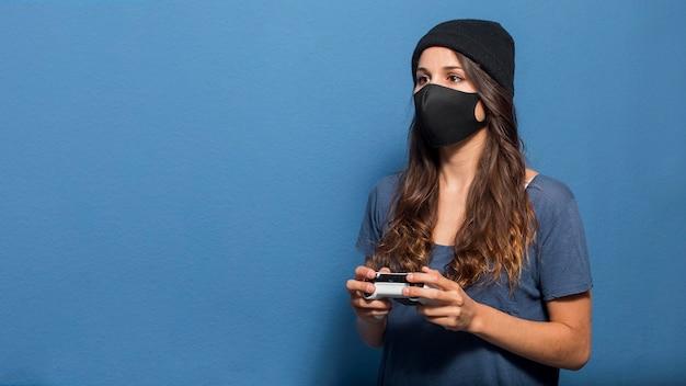 Kobieta ubrana w maskę i trzymając aparat