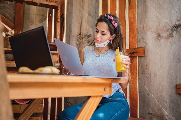 Kobieta ubrana w maskę i ubranie, czytanie ze szklanką soku