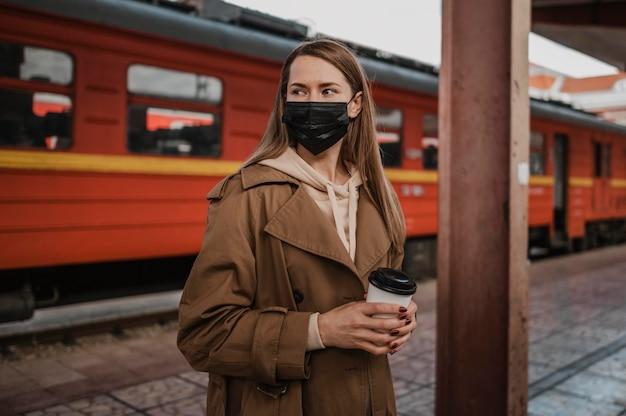 Kobieta ubrana w maskę medyczną na stacji kolejowej