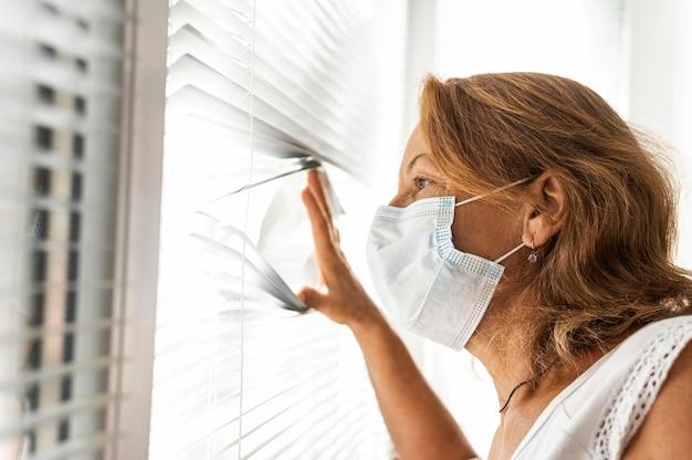 Kobieta ubrana w maskę medyczną, patrząc przez okno