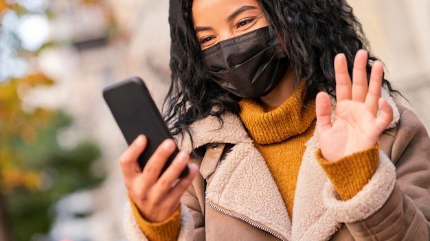 Kobieta ubrana w maskę medyczną podczas rozmowy wideo na swoim smartfonie