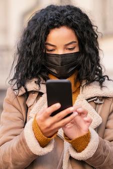 Kobieta ubrana w maskę medyczną podczas sprawdzania swojego telefonu