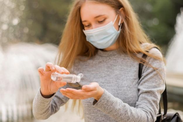 Kobieta ubrana w maskę medyczną siedząc obok fontanny