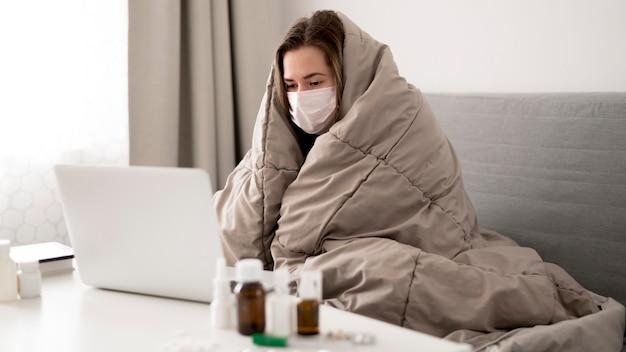 Kobieta ubrana w maskę medyczną zawiniętą w koc
