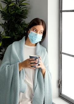 Kobieta ubrana w maskę na twarz w domu