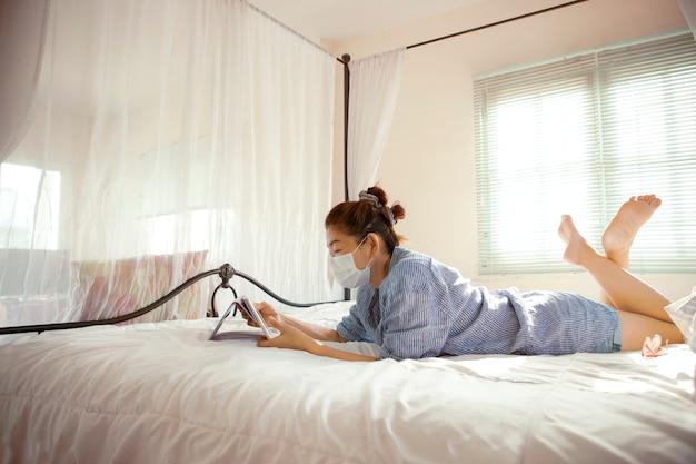 Kobieta ubrana w maskę ochronną czytanie wiadomości w komputerze typu tablet w sypialni domu