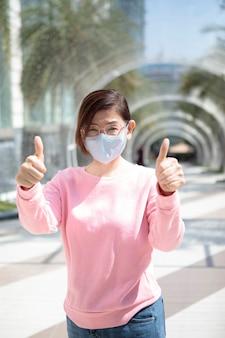 Kobieta ubrana w maskę ochronną stojącą na zewnątrz podnosząc rękę dla dobrego zdrowia