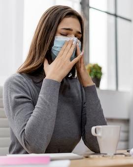 Kobieta ubrana w maskę podczas pracy w domu