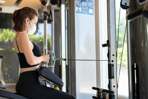 Kobieta ubrana w maskę siedzącą w rzędzie kabli, ciągnąc kabel maszyny do wiosłowania szkolenia w siłowni podczas pandermii wirusa koronowego.