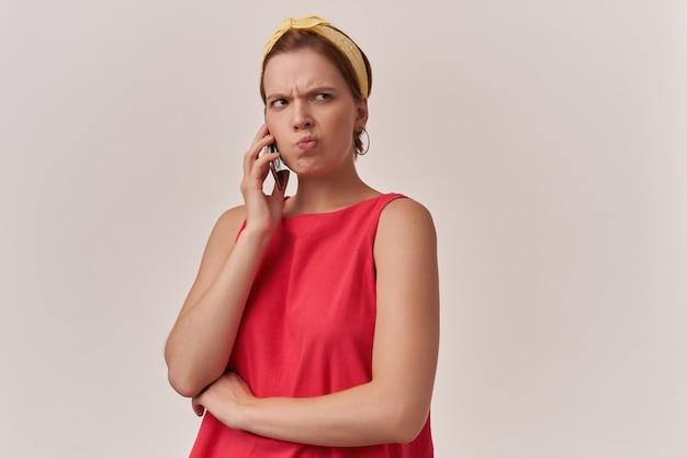Kobieta ubrana w modną czerwoną bluzkę i białą bandanę pozująca na ścianie emocja przypuszczenie myśl uważnie patrząc na bok skoncentrowany, zdyscyplinowany dotyk twarz