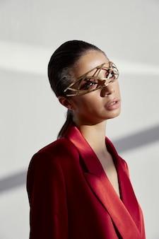 Kobieta ubrana w modne okulary, dekorację nową technologię, czerwony garnitur