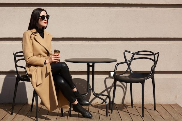 Kobieta ubrana w modny płaszcz po śniadaniu w przytulnej kawiarni na świeżym powietrzu i picia kawy z papierowego kubka