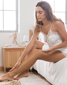 Kobieta ubrana w nocną sukienkę i używając kremu na nogach