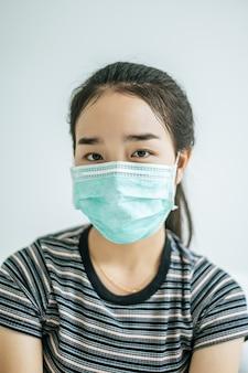 Kobieta ubrana w pasiastą koszulę w masce.