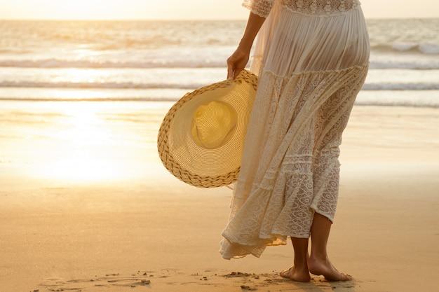 Kobieta ubrana w piękną białą sukienkę na plaży