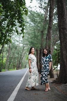 Kobieta ubrana w piękną długą sukienkę stojącą na drodze pod zielenią.