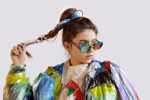 Kobieta ubrana w plastik na białej ścianie. modelki w ubraniach i butach ze śmieci. koncepcja mody, stylu, recyklingu, eko i ochrony środowiska. za dużo zanieczyszczeń, jemy i zabieramy.