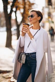 Kobieta ubrana w płaszcz i picia kawy