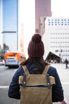 Kobieta ubrana w plecak stoi budynek