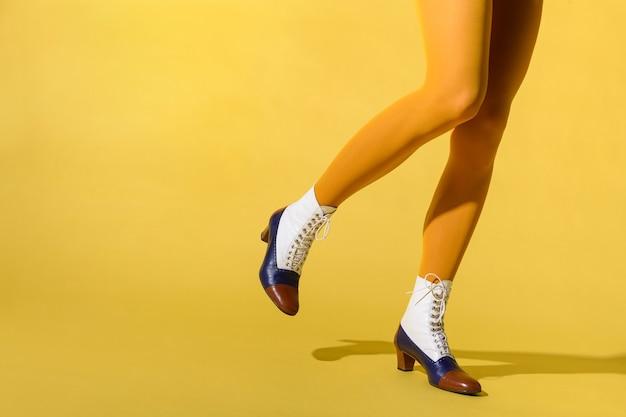 Kobieta ubrana w rajstopy w kolorze musztardy i buty retro tritone