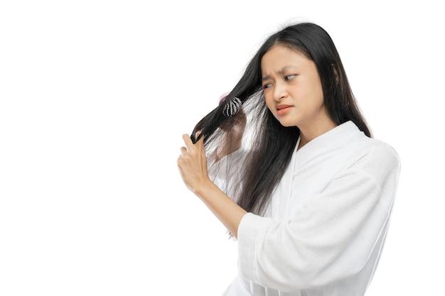 Kobieta ubrana w ręcznik denerwuje się, że jej włosy są splątane podczas czesania