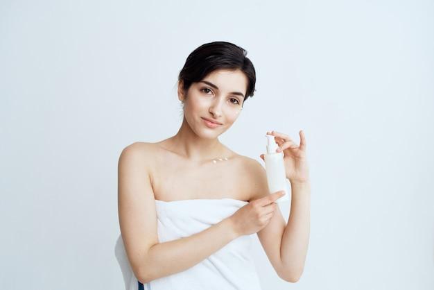 Kobieta ubrana w ręcznik trzymając butelkę balsamu z odkrytymi ramionami