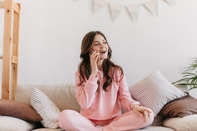 Kobieta ubrana w różową piżamę siedzi na kanapie otoczonej miękkimi poduszkami i rozmawia przez telefon