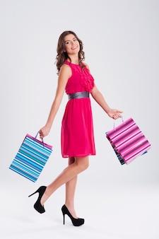 Kobieta ubrana w różową sukienkę trzymając torby na zakupy