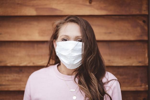 Kobieta ubrana w sanitarną maskę na twarz przed drewnianą ścianą