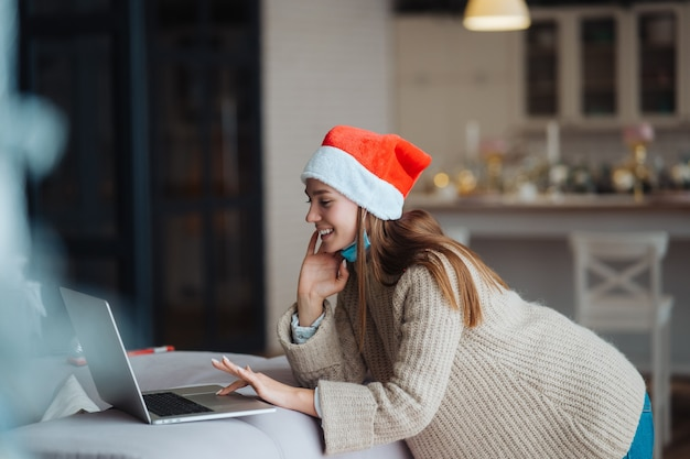 Kobieta ubrana w santa uśmiecha się podczas rozmowy z przyjacielem online na laptopie podczas obchodów bożego narodzenia w domu