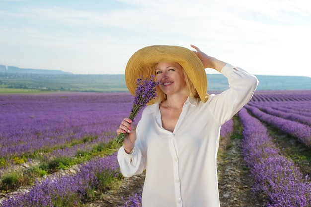 Kobieta ubrana w słomkowy kapelusz w lawendowym polu