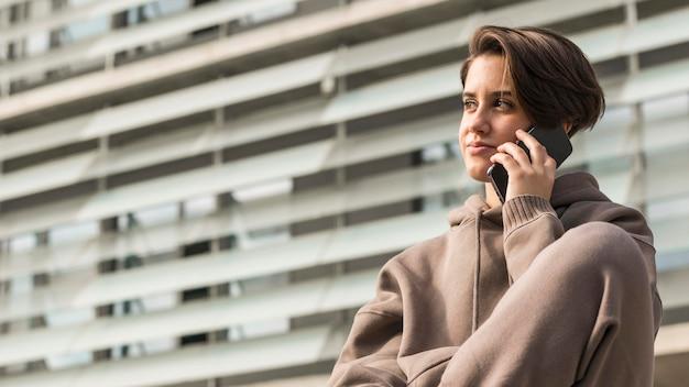 Kobieta ubrana w sportową i rozmawia przez telefon z miejsca na kopię