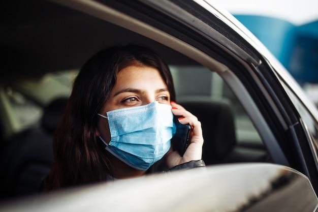 Kobieta ubrana w sterylną maskę medyczną w samochodzie taksówki na tylnym siedzeniu patrząc przez okno rozmawia przez telefon