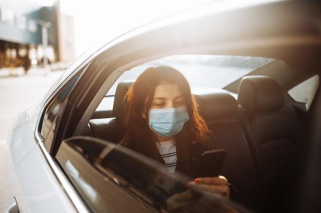 Kobieta ubrana w sterylną maskę medyczną w samochodzie taxi na tylnym siedzeniu, patrząc przez okno
