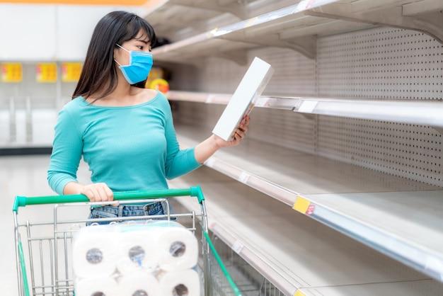 Kobieta ubrana w sterylną maskę przed pustymi półkami