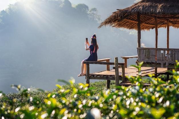 Kobieta ubrana w strój plemienia wzgórza siedzi na chacie w polu zielonej herbaty.