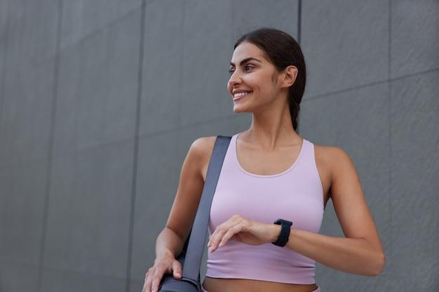 Kobieta ubrana w strój sportowy ma na sobie smartwatch niosący zwinięty karemat odwraca wzrok z delikatnymi uśmiechami przy szarej ścianie będąc w dobrym nastroju