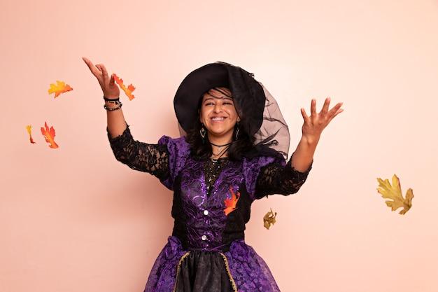 Kobieta ubrana w strój wiedźmy pozuje i rzuca w powietrze suche liście na jednolitym tle