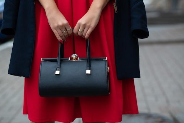 Kobieta ubrana w stylową czerwoną sukienkę i płaszcz, trzymając czarną skórzaną torebkę. pusta przestrzeń