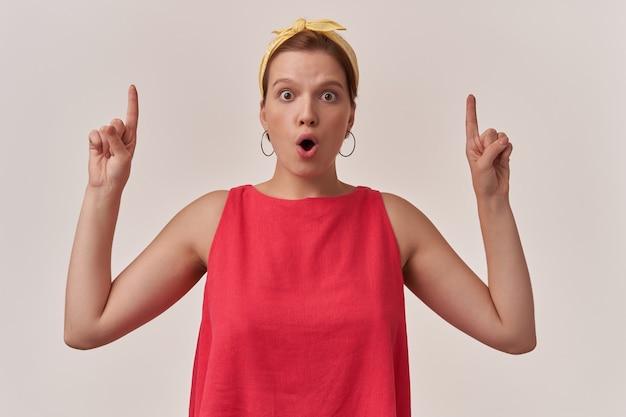 Kobieta ubrana w stylową modną czerwoną sukienkę i żółtą chustkę na białym tle na białej ścianie z palcami skierowanymi w górę emocja wow niespodzianka uwaga spojrzeć w górę