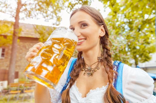 Kobieta ubrana w sukienkę dirndla pije piwo w bawarskim ogródku piwnym