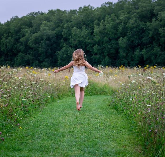 Kobieta ubrana w sukienkę i biegająca przez pole